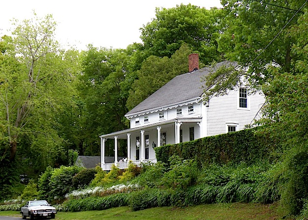 White House with porch on a green leafy hill in Sandwich MA