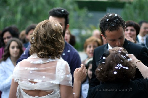 Italian weddings greeting the bride and groom with rice pasta and the bride and groom are covered in confetti in an italian wedding m4hsunfo