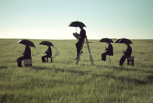 5 people holding black umbrellas overhead in the middle of a sunny field while seated on boxes and ladders