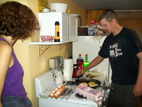 20090829 - Evan's parents' cabin - (by Tabbitha) - Svetlana, Jesse - cooking eggs, bacon - 3886132140_f2cab069e6_b