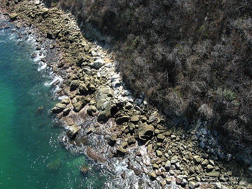 Straight down view of the rocky shoreline and green-blue waters near Playa Tejoncito, Huatulco, Mexico.