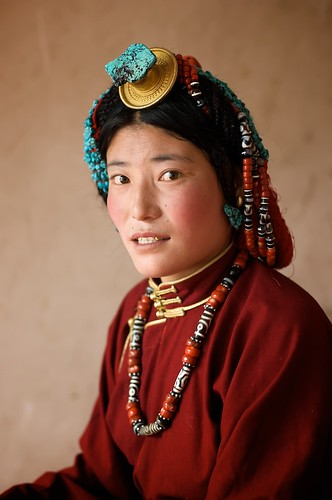 A portrait of a Tibetan woman with jewelry and gold front teeth in Tibet.