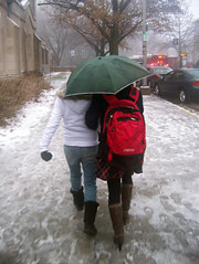 Two girls walking arm-in-arm under an umbrella...