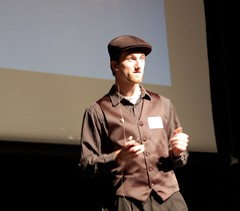 Article image: Chris Jones stands on stage during his presentation at the MLTI Student Conference.