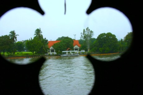 A house across the Pasig River as seen through a decorative wall panel at the Rizal Hall.
