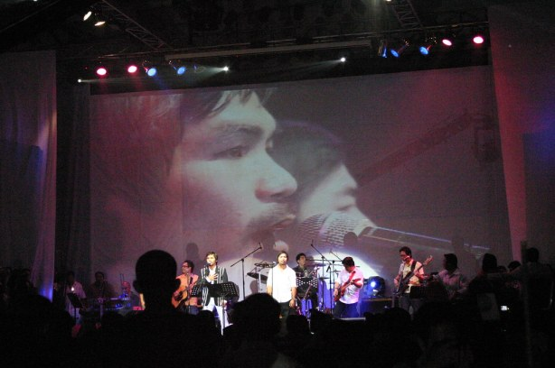 """""""A GIANT SCREEN SHOWS THE LIVE FOOTAGE OF MANNY PACQUIAO AND COMPOSER LITO CAMO PERFORMING ON STAGE.  BOTH SANG ABOUT 15-20 SONGS."""""""