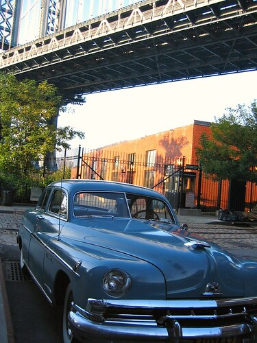 A classic car which seemed to be painted the same color as the Manhattan Bridge behind it.