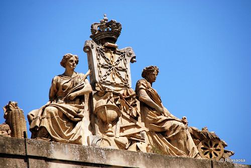 Grupo escultórico situado en lo alto del edificio del INAP (Instituto Navarro de Administración Pública), antigua Escuela de Comercio, situado en la calle Navarrería, frente a la Catedral.