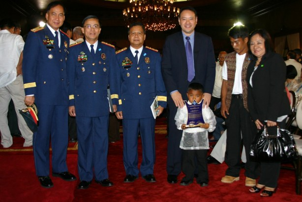 6-year old Angelo Lungkay, of Barangay Desawo, Tboli, South Cotabato, the youngest 2009 Gawad Kalasag Awardee carry his plaque he got from PGMA earlier while posing for the camera with Defense Secretary Gilbert Teodor, PNP 12 Regional Director Jake Cataluna, his father, among others.