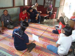 PMI volunteers explain to local family how to prevent malaria