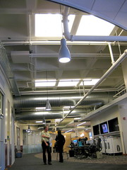 Old suspended ceiling removed as part of renovation to expose original pre-cast ceiling/floor. Honeycomb cells and other uneven surfaces help attenuate ambient noise. Light from ceiling squares are actually skylights through roof. Ductwork is insulated internally.