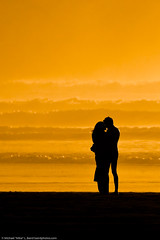 Lovers embracing on the beach at sundown / sun...
