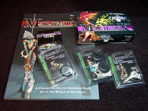 My starting collection of Malifaux miniatures, cards and rulebook