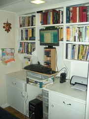 Computer set up with CPU on floor, keyboard & mouse on top of printer stand & in/out tray & shelf, monitor on cd rack (turned on end) and bookshelves behind it all
