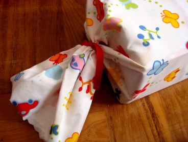 1 yard of Ikea fabric, wave-cut, rubber bands at both ends & finished with ribbons