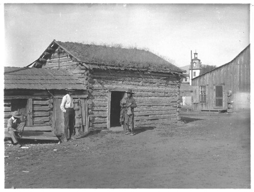 Three Indian Men in Front of a Cabin