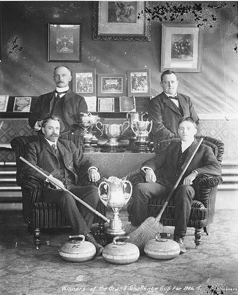 Curling team sitting around trophies, Dawson, Yukon Territory