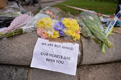 """Floral tributes with a message reading """"We are not afraid, our hearts are with you"""", are seen near a police cordon in Westminster in central London on March 23, 2017 a day after a deadly terror attack killed at least three people.  Britain's parliament re"""