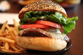 Primer pla d'una hamburguesa amb pa de sègol, enciam, tomàquet, formatge, la seva bona llesca de carn i acompanyada d'unes patates fregides