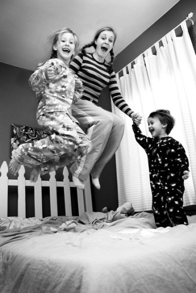 family jumping on a bed