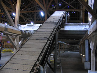 A wooden conveyor belt rises up in the center of the picture, amidst crossbeams in a large, barnlike structure.