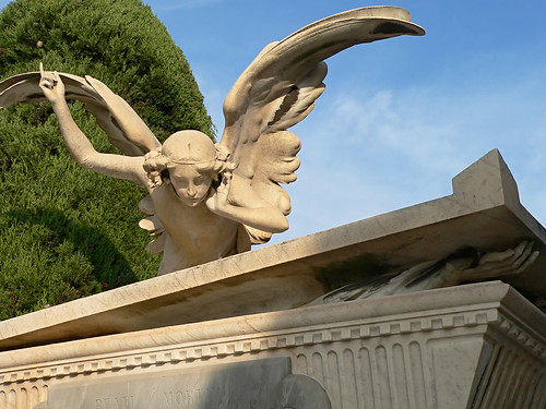 angel ontop a tomb, pointing up with on hand, his other hand cupped his ear