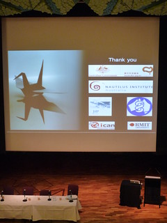 Screen showing a paper crane with sponsors logos, and a speakers podium in front.