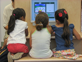 Three girls in front of a computer screen