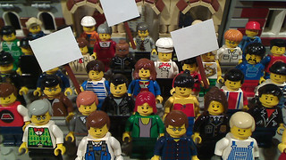 Crowd scene composed of lego people, some carrying signs.