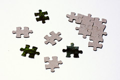 Scattered puzzle pieces next to solved fragment