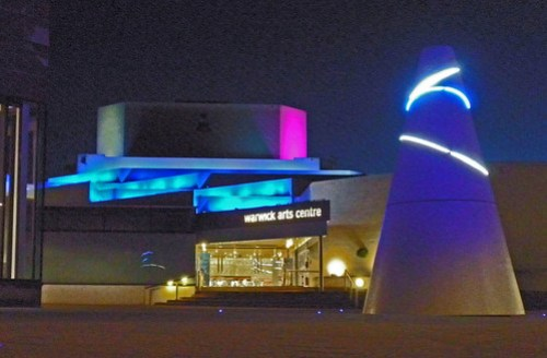 Night-time photo of the University of Warwick's Arts Centre with the white Koan in the foreground.