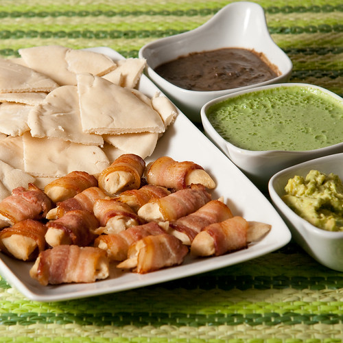 Chicken in bacon with pita and assorted dips.