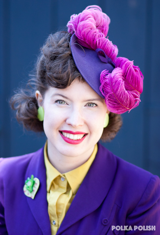 Purple felt 1940s tilt hat topped with a swirl of raspberry pink ostrich feathers, paired with a purple shirt and chartreuse blouse