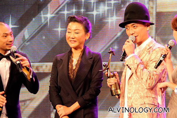 Bosco Wong getting his award on stage from Pauline Lan