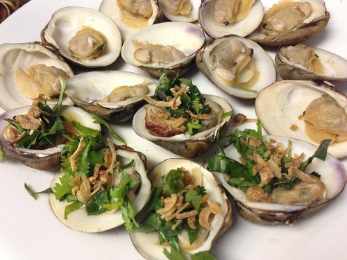 Grilled clams topped with basil, crispy shallots, scallion oil and nuoc mam sauce