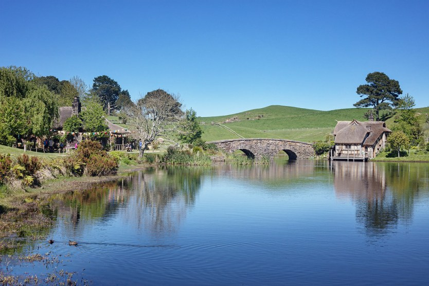 View of the lake with the Green Dragon Inn to the left. - Hobbiton in Photos