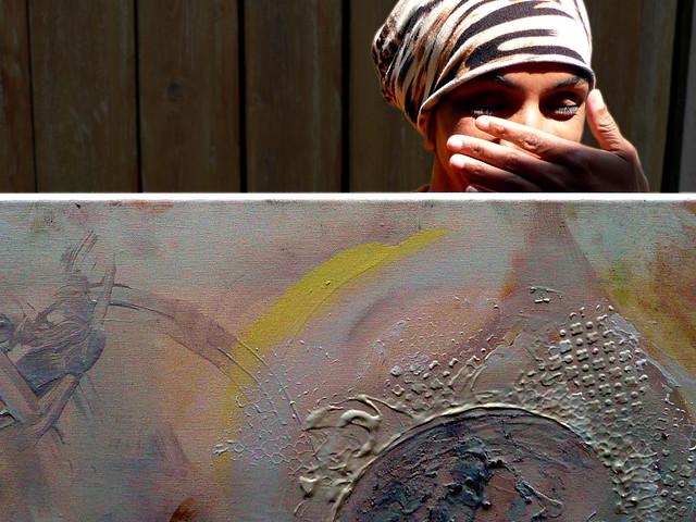 Achter één van haar schilderijen.