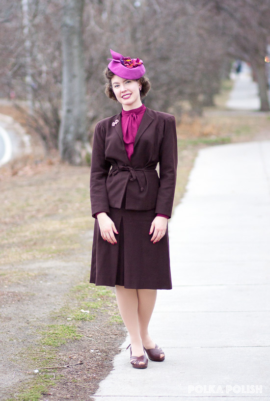 1940s chocolate brown suit paired with a raspberry pink blouse and hat
