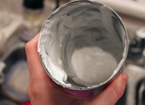 A hand holding a mostly empty jar of coconut cream; there's a bit left on the bottom and some scrapings on the sides.