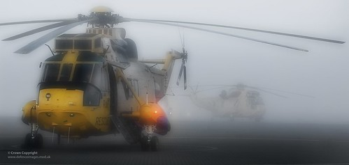 Two Sea Kings HAR3/3A helicopters, sat on the pan at RAF Valley in the early evening fog by Defence Images