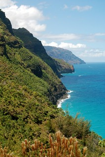 Portrait shot of the steep green cliffs and turquoise sea of Kauai's Na Pali coast.