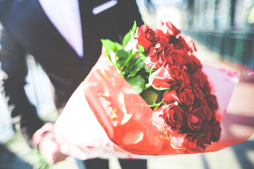 Imagen gratis de un hombre sujetando un ramo de rosas