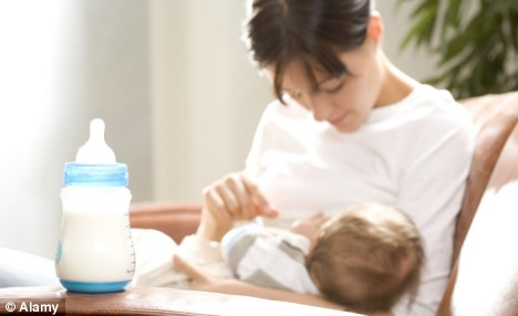 softfocus background mother and child possibly nursing (unclear), foreground big shiny clean bottle with white milk in it and attached feeding teat