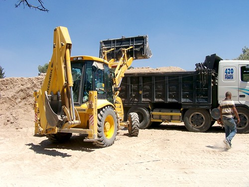 Bulldozer loading truck with dirt from the C4 dump pile