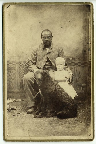 Black man with white child and dog