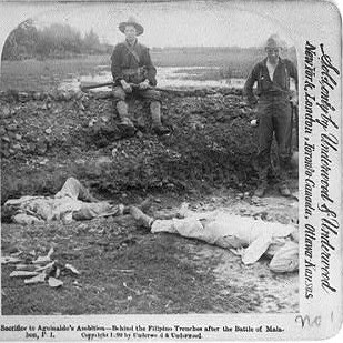 US soldiers posing for a photo by dead Filipinos.