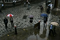People walk in the rain in central London's financial center.