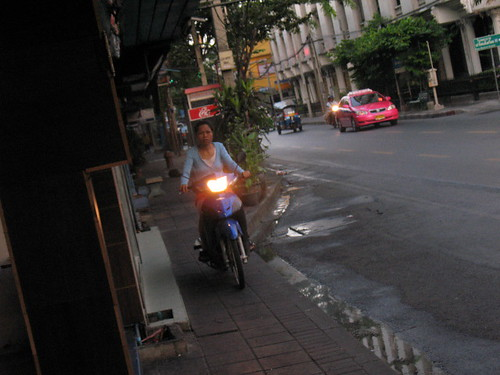woman riding motorcycle on the sidewalk