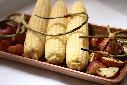 Platter of grilled garlic scapes, roasted potatoes and corn