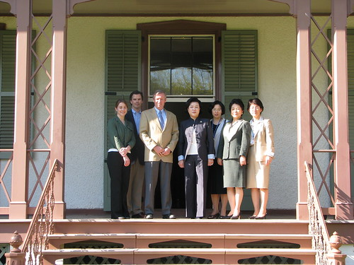 First Lady of Korea, Kim Yun-ok, poses with her guests and site staff on the veranda at President Lincoln's Cottage.
